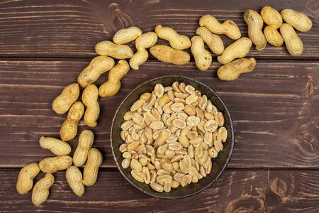 Lot of whole lot of halves of natural yellow peanut in dark ceramic bowl flatlay on brown wood