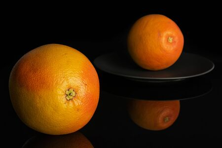 Group of two whole fresh pink grapefruit on gray ceramic plate isolated on black glass Imagens