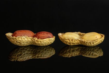 Group of four whole two pieces of natural yellow peanut isolated on black glass Imagens