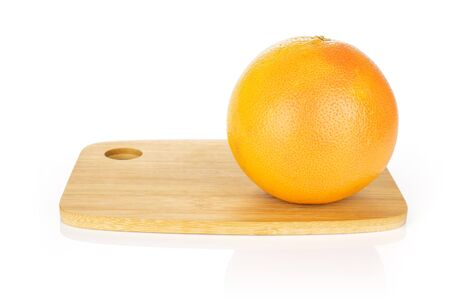 One whole fresh pink grapefruit on bamboo cutting board isolated on white background