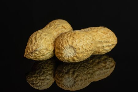 Group of two whole natural yellow peanut isolated on black glass