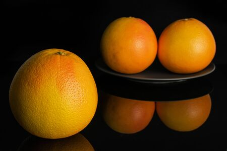 Group of three whole fresh pink grapefruit on gray ceramic plate isolated on black glass