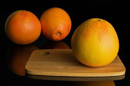 Group of three whole fresh pink grapefruit on bamboo cutting board isolated on black glass