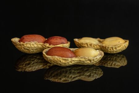 Group of six whole three pieces of natural yellow peanut isolated on black glass Imagens