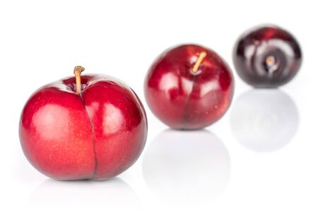 Group of three whole ripe red round plum placed diagonally in line isolated on white