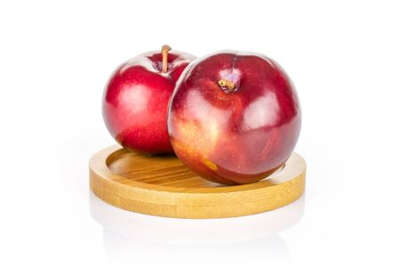Group of two whole ripe red round plum on round bamboo coaster isolated on white