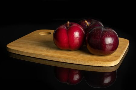 Group of three whole ripe red round plum on bamboo cutting board isolated on black glass