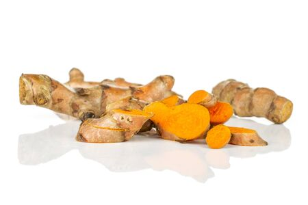 Lot of whole lot of slices of bright turmeric rhizome isolated on white background