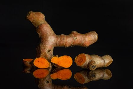 Group of one whole one half three slices of fresh bright turmeric rhizome isolated on black glass