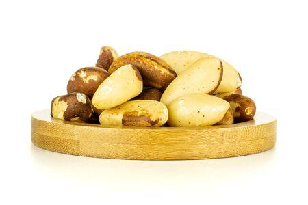 Lot of whole fresh unshelled brazil nut on bamboo plate isolated on white background