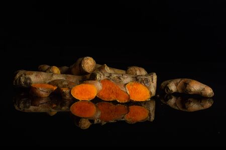 Group of lot of whole three slices of bright turmeric rhizome isolated on black glass