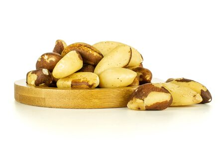 Lot of whole unshelled brazil nut on bamboo plate isolated on white background