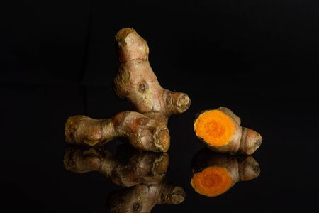 Group of two whole one half of pungent bright turmeric rhizome isolated on black glass Stock Photo
