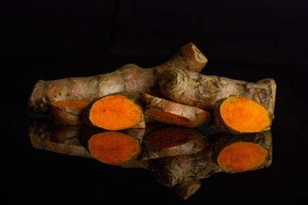 Group of two whole three slices of ripe bright turmeric rhizome isolated on black glass