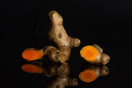 Group of two whole one half one slice of pungent bright turmeric rhizome isolated on black glass Stock Photo