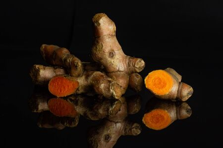Group of lot of whole one half one slice of bright turmeric rhizome isolated on black glass