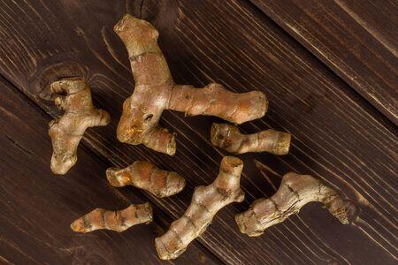 Lot of whole bright turmeric rhizome flatlay on brown wood