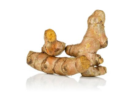 Group of three whole piquant bright turmeric rhizome isolated on white background