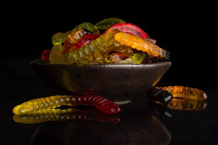 Lot of whole bright colourful jelly worm candy on grey ceramic plate isolated on black glass