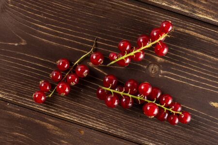 Lot of whole fresh red currant flatlay on brown wood