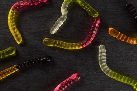 Lot of whole colourful jelly worm candy flatlay on grey stone