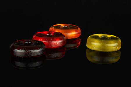 Group of four whole colourful hard candy dark red cherry orange yellow isolated on black glass Фото со стока