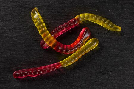 Group of three whole crimson yellow colourful jelly worm candy flatlay on grey stone Фото со стока