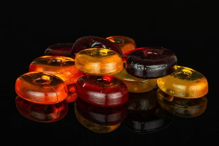 Lot of whole colourful hard candy isolated on black glass
