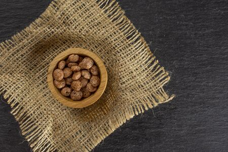 Lot of whole chocolate ball breakfast cereals in wooden bowl on jute cloth flatlay on grey stone