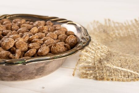 Lot of whole chocolate ball breakfast cereals in old iron bowl on jute cloth on white wood Banque d'images
