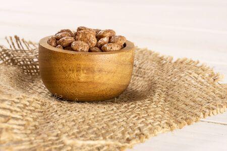 Beaucoup de céréales de petit déjeuner boule de chocolat entières dans un bol en bois sur toile de jute sur bois blanc
