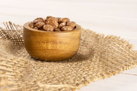 Lot of whole chocolate ball breakfast cereals in wooden bowl on jute cloth on white wood