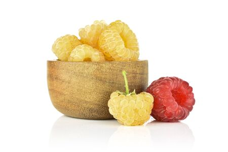 Lot of whole fresh golden hymalayan raspberry with one red berry in wooden bowl isolated on white background