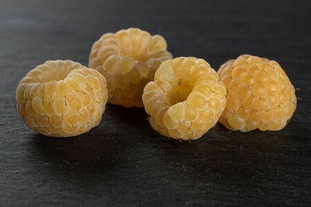 Group of four whole fresh golden hymalayan raspberry on grey stone