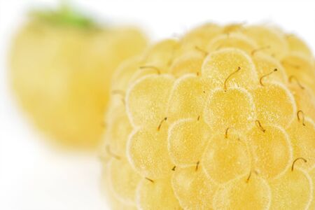 Closeup of two whole fresh golden hymalayan raspberry isolated on white background