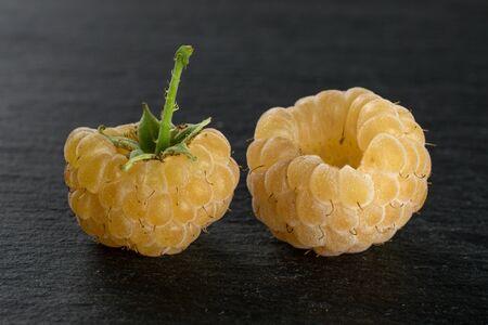 Group of two whole fresh golden hymalayan raspberry on grey stone Stok Fotoğraf