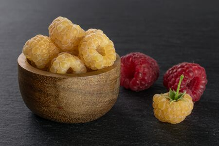 Lot of whole fresh golden hymalayan raspberry with two red berries in wooden bowl on grey stone