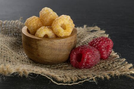 Lot of whole fresh golden hymalayan raspberry with two red berries in wooden bowl on jute cloth on grey stone Stok Fotoğraf