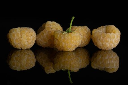 Group of five whole fresh golden hymalayan raspberry isolated on black glass