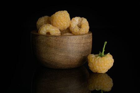 Lot of whole ripe fresh golden hymalayan raspberry in wooden bowl isolated on black glass