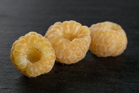 Group of three whole fresh golden hymalayan raspberry on grey stone