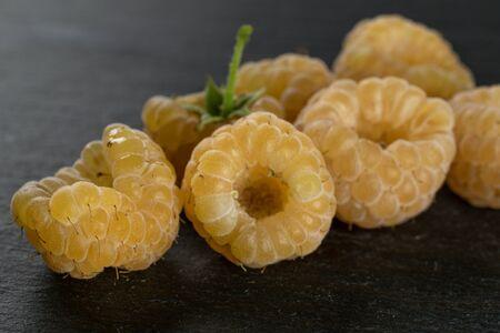 Lot of whole fresh golden hymalayan raspberry on grey stone