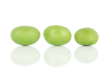 Group of three whole green sugared nut dragee isolated on white background