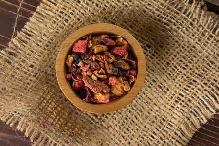 Lot of pieces of lavender strawberry ice tea in wooden bowl on jute cloth flatlay on brown wood Banque d'images
