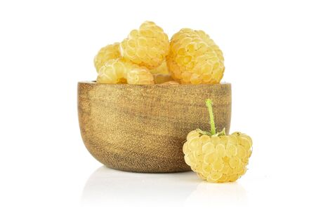 Lot of whole ripe fresh golden hymalayan raspberry in wooden bowl isolated on white background