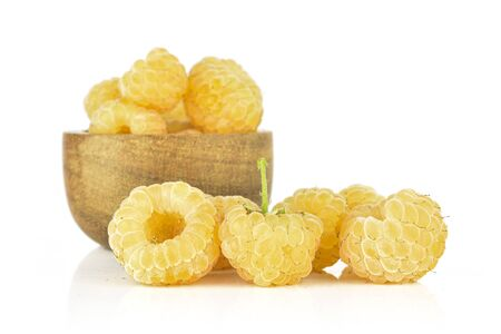 Lot of whole fresh golden hymalayan raspberry in wooden bowl isolated on white background