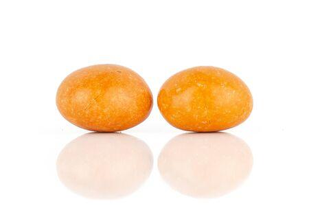 Group of two whole orange sugared nut dragee isolated on white background