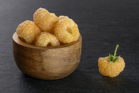 Lot of whole ripe fresh golden hymalayan raspberry in wooden bowl on grey stone
