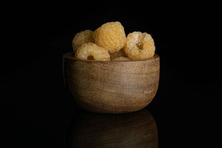 Lot of whole fresh golden hymalayan raspberry in wooden bowl isolated on black glass