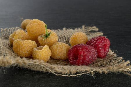 Lot of whole fresh golden hymalayan raspberry with two red berries on jute cloth on grey stone